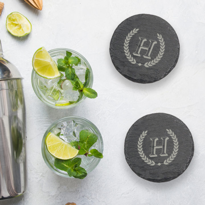 round slate coasters on top of table next to mojitos