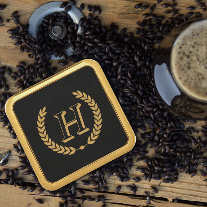 SQUARE LEATHERETTE COASTER WITH METAL EDGE ON TOP OF COFFEE BEANS NEXT TO CUP OF COFFEE