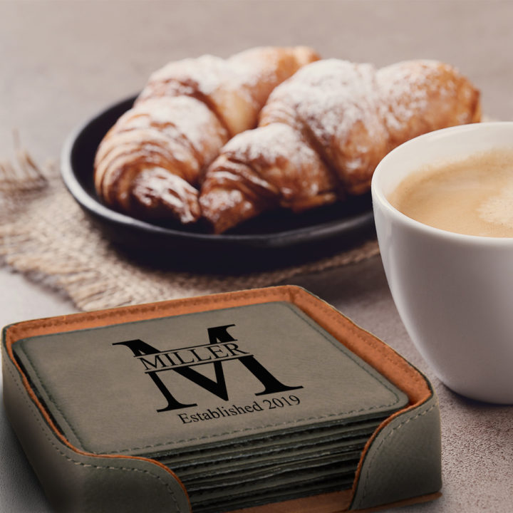 Personalized Miller Design Square Leatherette Coaster Set of 6 on table next to cup of coffee and crossaint