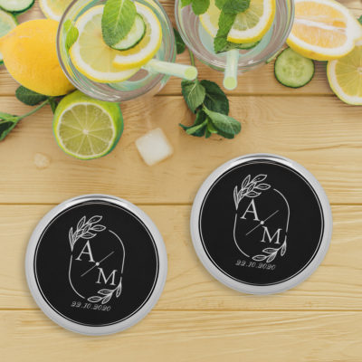 black leatherette coaster sets on top of wood table next to glasses of cold lemonade