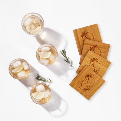 bamboo coaster set on white surface next to cold mixed drinks